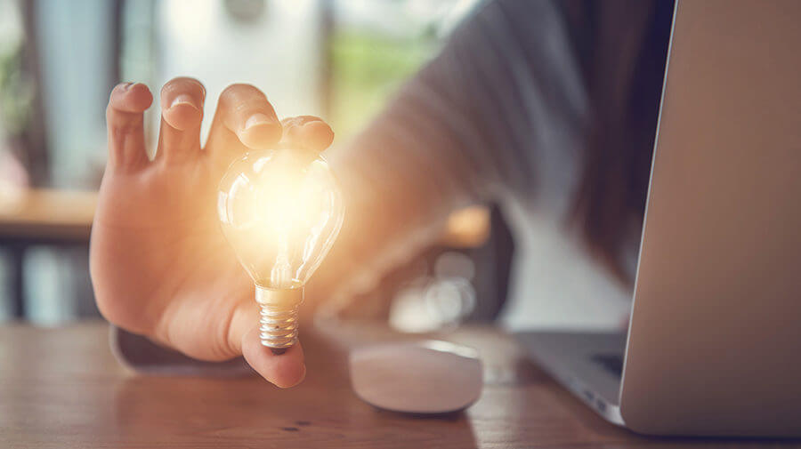 Person at Laptop Holding Lightbulb To Represent Turning Website Visitors Into Subscribers and Clients