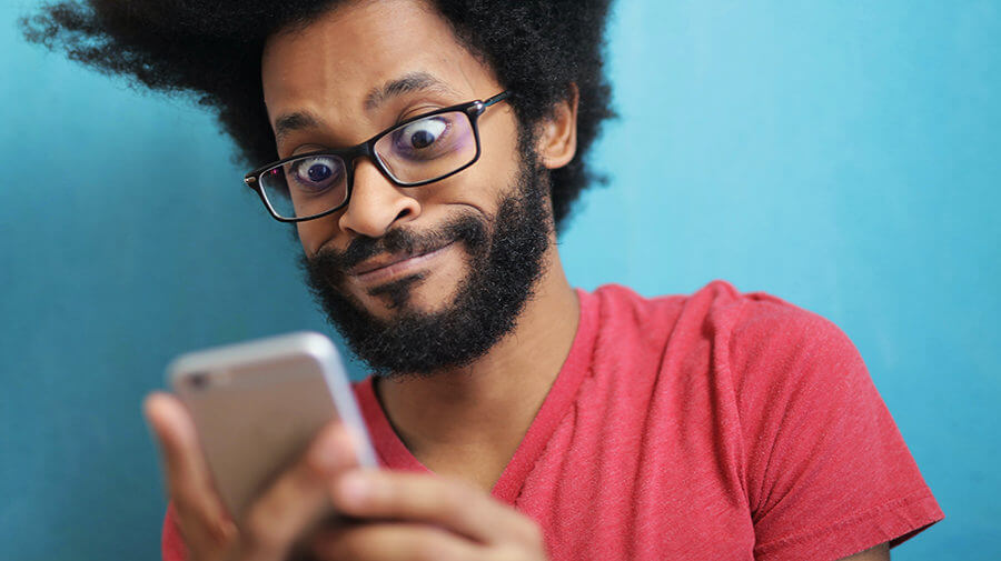 Shocked man looking at smartphone, Can't believe what is posted on social media